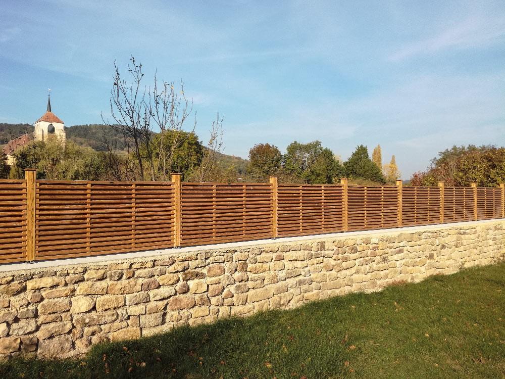 Brise vue bois Arifi Pin classe 4 technologie DURAPIN marque PIVETEAUBOIS sur muret en pierre Vivre en Bois
