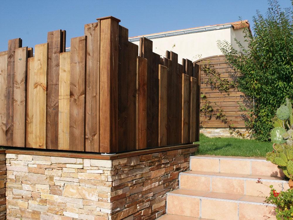 Palissade bois Nymphéa Pin classe 4 technologie DURAPIN marque PIVETEAUBOIS sur muret de pierres Vivre en Bois