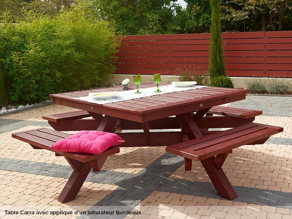 Table pique-nique en bois avec applique d'un saturateur bordeaux. Vendue non peinte
